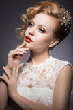 Portrait of a beautiful ginger woman with red lips in the image of the bride. Royalty Free Stock Images