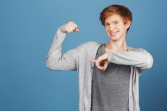 Portrait of beautiful ginger young guy on blue background wearing casual grey outfit pointing with index finger on his. Muscles, looking in camera with happy Stock Images