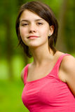 Portrait of beautiful girl. Young beautiful girl in red vest costs on glade of green summer wood Royalty Free Stock Photography