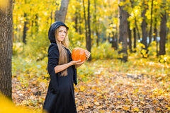 Portrait of beautiful girl as witch dressed in a dress with a hood. Halloween, carnival, holidays, autumn and people. Portrait of beautiful girl as witch dressed Stock Images