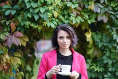 Portrait of beautiful girl in autumn in park. With a cup Royalty Free Stock Photography