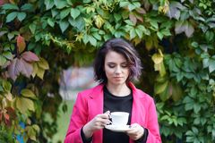 Portrait of beautiful girl in autumn in park. With a cup Royalty Free Stock Image