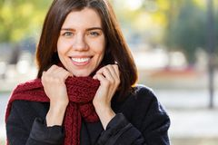 Portrait of a beautiful girl in an autumn park in a red scarf, holding on to a scarf. stock images