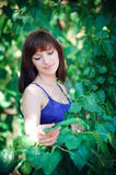 Portrait of a beautiful girl on a background of green leaves Stock Photography