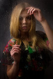 Portrait of a beautiful girl behind wet glass Stock Photography