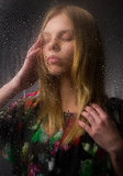 Portrait of a beautiful girl behind wet glass Royalty Free Stock Images