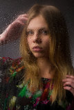 Portrait of a beautiful girl behind wet glass Stock Image