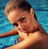 Portrait of beautiful girl with blond hair posing in swimming pool Stock Photos