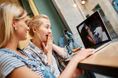Portrait of beautiful girl blonde and charming Asian girl sitting in cafe and watching photos on laptop which they did on. Vacation stock image