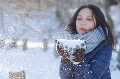 Portrait of a beautiful girl blowing the snowflakes from her hands. Portrait of pretty girl blowing the snowflakes from hands Stock Image