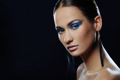 Portrait of beautiful girl with blue bright make-up in long earrings Royalty Free Stock Photo