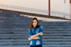 Portrait of a beautiful girl in blue on stairs Royalty Free Stock Photography