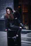 Portrait of a beautiful girl with brown eyes in glasses in a black hat and coat with fur sits on a barrel in the Stock Photo