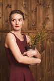 Portrait of a beautiful girl in a burgundy dress. On a background of a wooden wall holding a vase of flowers Stock Photography