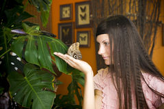 Portrait of beautiful girl with butterfly in a greenhouse Royalty Free Stock Photo