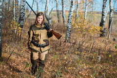 Portrait of a beautiful girl in camouflage hunter with shotgun stock images