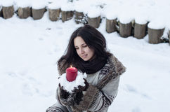 Portrait of a beautiful girl with candle in snow Stock Image
