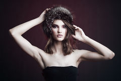 Portrait of a beautiful girl in a cap of black fox. Stock Image