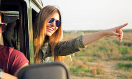 Portrait of beautiful girl on car roadtrip pointing forward. Stock Images