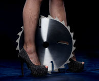 Portrait of beautiful girl with circular saw blade. Bretty woman legs, mesh stockings, black heeled shoes, sawblade stock photography