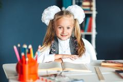 Portrait of a beautiful girl in the classroom. Little schoolgirl with white bows sitting at the table and studying. Education and stock images