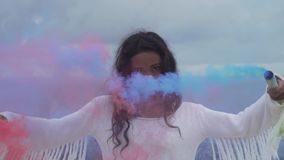 Beautiful girl with colored smoke. Portrait of beautiful girl with colored smoke playing at the mountain field over ocean and cloudy sky background - video in stock video