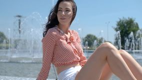 Portrait of beautiful girl in colorful summer clothes sitting near a fountain stock footage