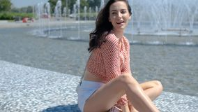 Portrait of beautiful girl in colorful summer clothes sitting near a fountain stock video footage