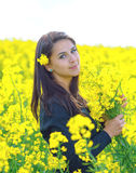 Portrait of a beautiful girl in the colza field in summer Stock Photo
