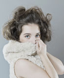 Portrait of beautiful girl covering the face fur hood. Studio photography on a light gray background Royalty Free Stock Photo