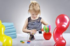 Portrait of beautiful girl cutting paper with scissors. Royalty Free Stock Photography