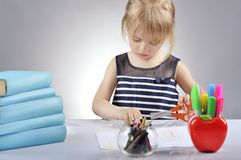 Portrait of beautiful girl cutting paper with scissors. Royalty Free Stock Photo