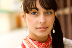 Portrait of beautiful girl with dark hair. Young beautiful woman with big earrings smiles Stock Images