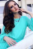 Portrait of beautiful girl with dark hair in blue silk dress Stock Photo