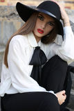 Portrait of beautiful girl with dark hair in elegant blouse and hat Stock Photo