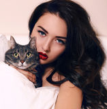 Portrait of beautiful girl with dark hair posing with cat Royalty Free Stock Photos