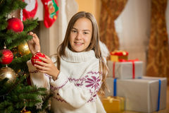 Portrait of beautiful girl decorating Christmas tree with bauble Royalty Free Stock Images
