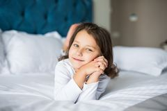 Portrait of beautiful girl, dreaming in bed. Beauty little girl in bed at home. Royalty Free Stock Photos