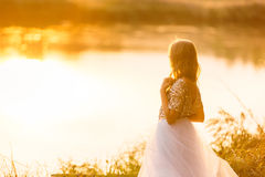 Portrait of a beautiful girl in a dress at sunset near a lake Stock Photo