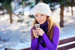 Portrait of the beautiful girl drinking. Hot beverage in snowy winter Stock Image