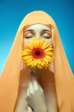 Portrait of beautiful girl with the flower. Portrait of beautiful woman in the shawl with the orange flower Stock Images