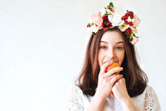 Portrait of beautiful girl with flower wreath eating apple Stock Photos
