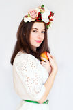 Portrait of beautiful girl with flower wreath holding apple stock photography