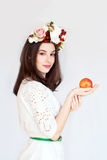 Portrait of beautiful girl with flower wreath holding apple royalty free stock image