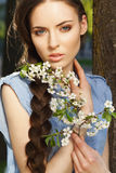 Portrait of beautiful girl with flowers. Portrait of a beautiful girl with braid hairdo and flower in her hand, looking at camera, outdoors Royalty Free Stock Images