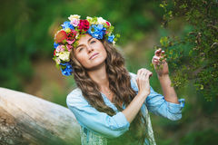 Portrait of a beautiful girl with a flowers on a head. Portrait of a beautiful girl with a diadem of a flowers on a head on a nature background Stock Images