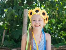 Portrait of beautiful girl with flowers of sunflowers on his head. Royalty Free Stock Photos