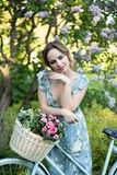 Portrait of a beautiful girl in the forest, holding a bike with a basket of flowers, behind the rays of the sun, a blue flowered stock image