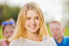 Portrait of beautiful girl, friends on background. Portrait of beautiful girl and friends on background sitting together in park on grass during autumn day Stock Photography