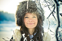 Portrait of a beautiful girl in a fur hat in backl. Cute portrait of a beautiful girl in a fur hat in backlit Royalty Free Stock Images